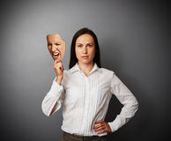 Quiet woman holding aggressive mask Stock Image