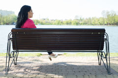Quiet woman sitting on bench Stock Photo