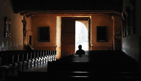Quiet Worship. Lone figure captured in a moment of quiet worship, Mission Basilica San Diego de Alcala. San Diego, CA stock photography