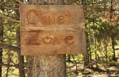 Quiet zone. Handmade wooden rustic notice of a quiet zone in a pine forest royalty free stock images
