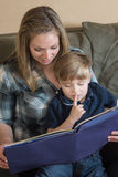 Quietly Reading. A mother and son enjoy quality time as she reads a book to him royalty free stock photo