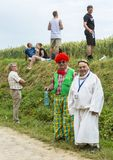 Disguised Spectators - Tour de France 2015. Quievy,France - July 07, 2015: Disguised spectators waiting for the cyclists on the side of the cobblestone road Stock Photo