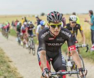 Andreas Schillinger Riding on a Cobblestone Road - Tour de Franc Stock Photo