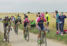 Group of Cyclists Riding on a Cobblestone Road - Tour de France. Quievy,France - July 07, 2015: Group of cyclists riding on a cobblestoned road during the stage Stock Photo