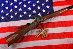 Quigley-Gewehr auf amerikanischer Flagge Lizenzfreie Stockfotografie