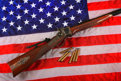 Quigley Rifle on American Flag. A Quigley Sharps 45-170 Caliber Rifle and a few bullets laying on an American flag.  Shallow depth of field Royalty Free Stock Photography