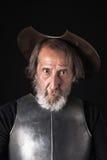 Quijote Gammal skäggig krigare med bröstharnesken och hjälmen Fotografering för Bildbyråer