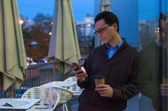 Quike断裂 英俊的微笑的商人身分、短信的消息和饮用的咖啡 站立与杯子的一个人的画象 免版税库存图片