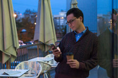 Quike break. Handsome smiling businessman standing, texting message and drinking coffee. Portrait of a man standing with a cup Royalty Free Stock Image