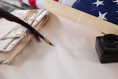 Quill feather and ink pot with legal documents arranged on table Royalty Free Stock Photo