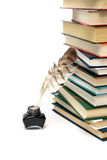 Quill in the inkwell and stack of  books on a white background Stock Images