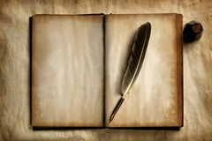 Quill on old book Stock Photography