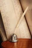 Quill pen. Antique quill pen and ledger book on wood table Stock Images
