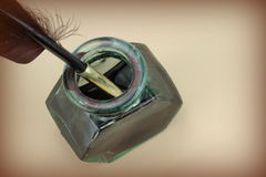Quill pen in glass ink bottle on a brown paper Royalty Free Stock Images