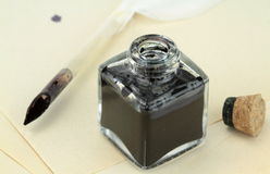 Quill pen and glass ink bottle Stock Images