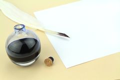 Quill pen, glass ink bottle and parchment Stock Images