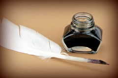 Quill pen and glass ink bottle Royalty Free Stock Image