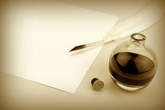 Quill pen and glass ink bottle with paper Stock Photography