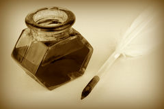 Quill pen and glass ink bottle, sepia style Stock Photos