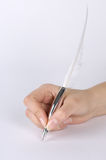 Quill pen in a hand Stock Photo