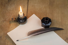 Quill  pen  and inkwell, and candlestick well resting on old paper. Literature concept Stock Images