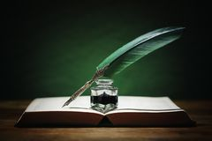 Quill pen and inkwell on old book stock photos