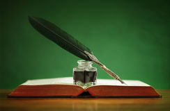 Quill pen and inkwell on old book. Quill pen and inkwell resting on an old book with green background concept for literature, writing, author and history Royalty Free Stock Photo