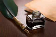 Quill pen, inkwell and paper. On wooden table Royalty Free Stock Images