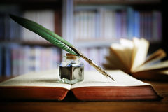 Quill pen on an old book in a library Stock Photos