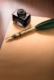 Quill pen and paper on wooden table Royalty Free Stock Photography