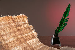 Quill pen and papyrus sheet. Green quill pen and a backlit papyrus sheet with its texture Stock Photo
