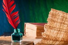 Quill pen and papyrus sheet. Red quill pen and a backlit papyrus sheet in a blue and green background Stock Photos