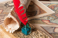 Quill pen and a papyrus sheet. Red quill pen, a green inkwell and a rolled papyrus sheet with some old maps on a wooden table Stock Image