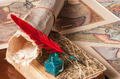 Quill pen and a papyrus sheet. Red quill pen, a green inkwell and a rolled papyrus sheet with some old maps on a wooden table Stock Photos