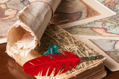 Quill pen and a papyrus sheet. Red quill pen, a green inkwell and a rolled papyrus sheet with some old maps on a wooden table Stock Images