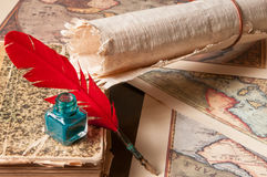 Quill pen and a papyrus sheet. Red quill pen, a green inkwell and a rolled papyrus sheet with some old maps on a wooden table Royalty Free Stock Image