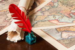 Quill pen and a papyrus sheet. Red quill pen, a green inkwell and a rolled papyrus sheet with some old maps on a wooden table Royalty Free Stock Photography