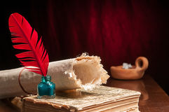 Quill pen and papyrus sheet. Red quill pen and a rolled papyrus sheet on an old book Royalty Free Stock Image