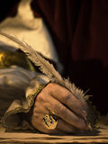 Quill and Signet Ring. A senior man's hand holding a quill and wearing a signet ring with seal Stock Photos