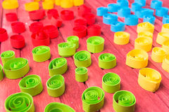 Quilling art. Color paper curls on the wooden table Stock Image