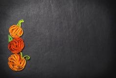 Quilling des potirons sur un fond noir Halloween Photo stock