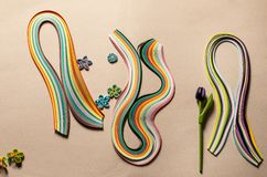 Quilling paper flowers and an artificial tulip against the background of paper quilling strips stock photo