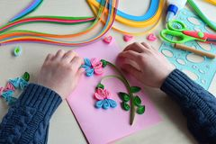 Quilling technique. Boy making decorations or greeting card. Paper strips, flower, scissors. Handmade crafts on holiday: Birthday,. Mother or Father Day, March royalty free stock photos