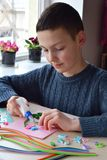 Quilling technique. Boy making decorations or greeting card. Paper strips, flower, scissors. Handmade crafts on holiday: Birthday stock photo
