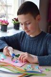 Quillingstechniek Jongen die decoratie of groetkaart maken Document stroken, bloem, schaar Met de hand gemaakte ambachten op vaka stock foto
