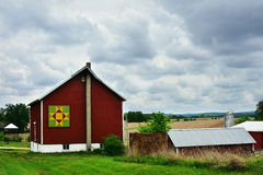 Quilt Barn with Storm Clouds. A red quilt barn with a green, yellow and red quilt on it with storm clouds in Wisconsin Stock Photo
