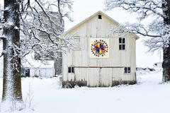 Quilt Barn in a Winter Snowy Wonderland. A beautiful white, rustic barn with a colorful quilt on it in a snowy, winter wonderland in Walworth County, Wisconsin Royalty Free Stock Photo