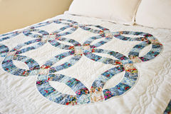 Quilt on bed. Traditional wedding ring patchwork quilt on a bed Stock Image