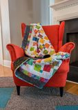 Quilt Draped Over Back of Orange Chair. In front of fire place royalty free stock images