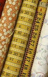 Quilt Fabric. Bolts of quilt fabric with tape measure and ruler along with orange and white pattern and faux embroidery stitches stock image